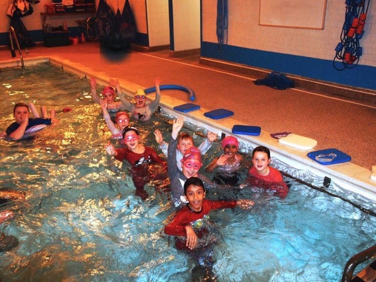Happy kids in the pool during swimming lesson