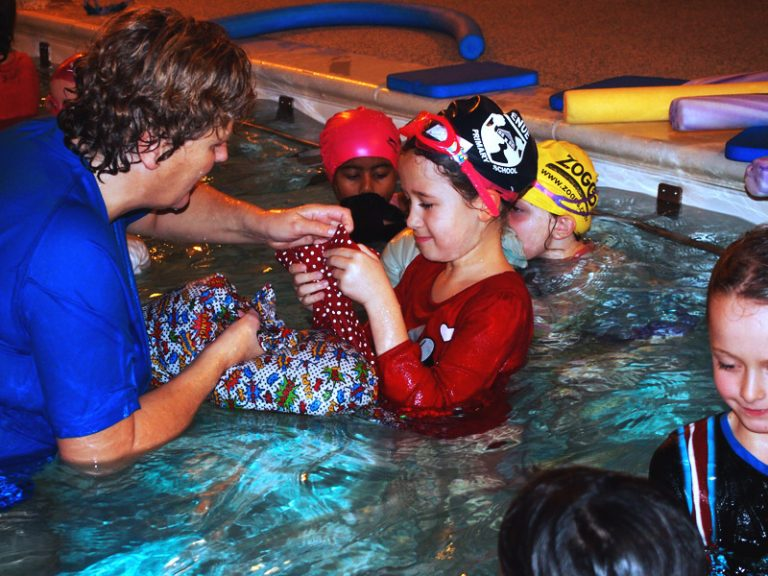 Teacher helps a child during swimming lesson
