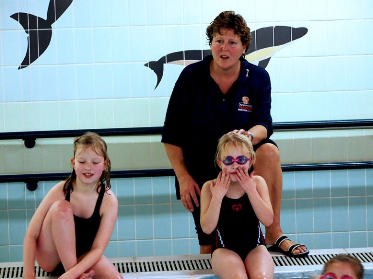Teacher with kids by the edge of the pool