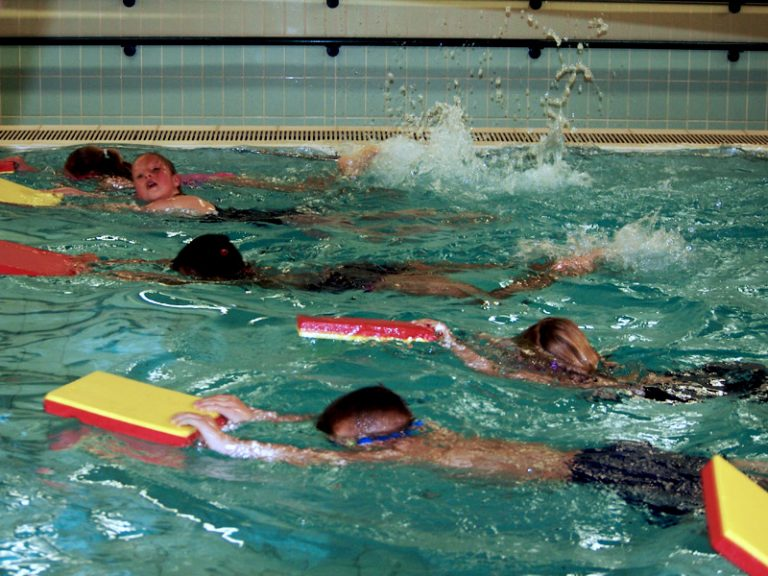 KIds swimming in the lane holding the boards