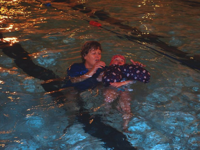 Teacher holds a child in the pool